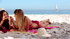 Attractive women laying together on the beach - stock footage