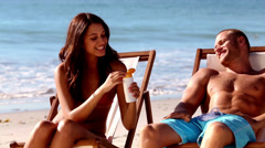Cheerful woman applying sunscreen to her boyfriend Stock Footage