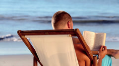 Man reading on the beach Stock Footage