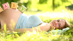 Pregnant woman lying in grass with baby blocks on her belly Stock Footage