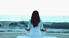 Woman practicing yoga in front of the sea - stock footage