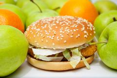 chicken burger next to many apples and oranges - stock photo