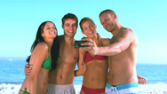 Group of friends taking self pictures on the beach Stock Footage