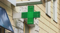 Pharmacy, drug store green neon cross lighted at daytime, city HD Footage
