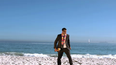 Businessman on the beach throwing his cocktail glass Stock Footage