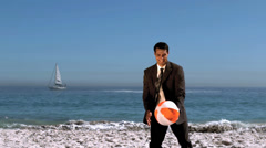 Attractive businessman playing with beachball Stock Footage