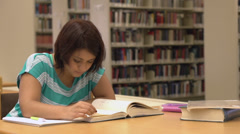 Female studying looks up and smiles Stock Footage