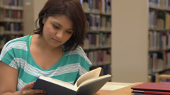 Young female reading book at library Stock Footage