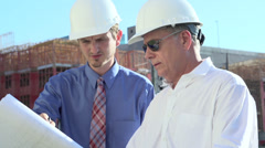 Engineers discussion print layout at site Stock Footage