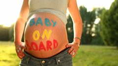 "Pregnant woman with ""baby on board"" written on baby belly - stock footage"
