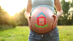Baby belly in sunlight with house painted on it - stock footage