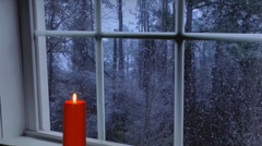 Red candle in front of window. Snowing outside Stock Footage