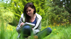 Woman sitting on grass writing on a notebook Stock Footage