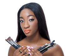 african beauty holding make up brushes - stock photo