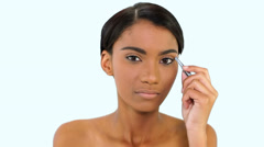 Stock Video Footage of Woman plucking eyebrow with tweezers