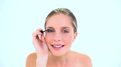 Blond woman making up her eye with mascara Stock Footage