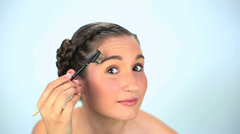 Young woman brushing her eyebrow Stock Footage