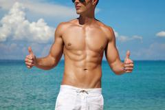 Thumbs up for a beach body Stock Photos