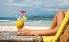 holding a cocktail on a tropical beach - stock photo