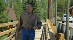 Man walks and stops on bridge walkway Stock Footage