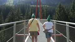 Couple crossing a suspended bridge Stock Footage