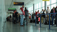 People wait at gate to board plane Stock Footage