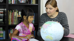 Homeschool Mom Teaching Asian Daughter Geography Lesson Stock Footage
