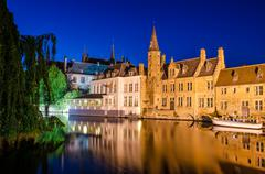 bruges canal at night and medieval houses with reflection in water - stock photo