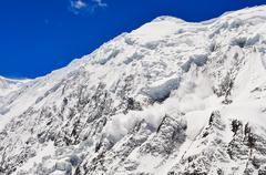 Avalanche falling from snowy frozen mountain peak Stock Photos