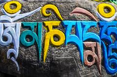 tibetan buddhist religious symbols on stones - stock photo