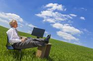 Stock Photo of businessman relaxing thinking at desk in green field