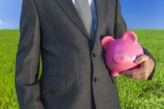 man businessman holding piggy bank in field - stock photo