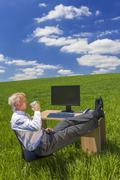 businessman relaxing drinking coffee or tea in green field desk - stock photo