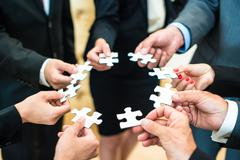 Teamwork - Business people solving a puzzle Stock Photos