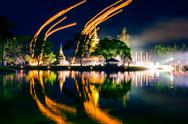 Stock Photo of light lampions at night above buddhist temple in sukhothai historical park