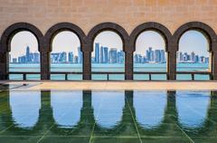 doha skyline through the arches of the museum of islamic art, doha - stock photo