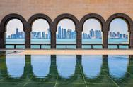 Stock Photo of doha skyline through the arches of the museum of islamic art, doha