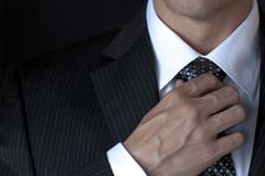 Businessman adjusting tie with right hand Stock Photos