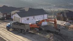dump-truck loading with excavator, new neighbourhood, wide shot - stock footage