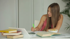 Student girl studying at table and eating snacks Stock Footage