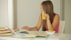 Charming girl studying at table and drinking juice Stock Footage
