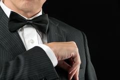 man in tux tucks in pocket square - stock photo