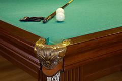 billiard table, hole, balls, cue and glove on green cloth - stock photo
