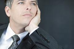 confident businessman gazes off camera - stock photo