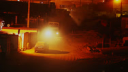 Stock Video Footage of Construction site at night, trucks lorries drive in out, yellow