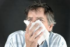 Man sneezing into tissue Stock Photos