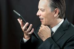 businessman admires tablet - stock photo