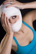female holds face first aid gauze wrapped head injury pain - stock photo