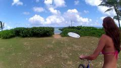 HAWAII COOL AERIAL OF BEACH FOLLOWING GIRL ON BIKE IN TROPICS HD Stock Footage