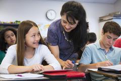 Teacher helping students in class Stock Photos